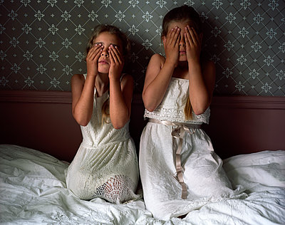 Two girls covering eyes with hands - p945m1155032 by aurelia frey