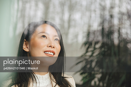 Smiling mid adult businesswoman looking up through window at office - p426m2101946 by Maskot