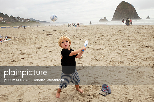 Caucasian boy playing on beach - p555m1410875 by Roberto Westbrook
