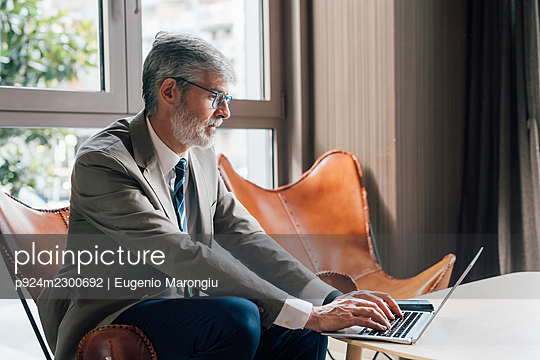 Italy, Businessman using laptop in creative studio - p924m2300692 by Eugenio Marongiu