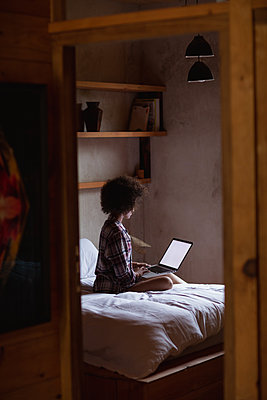 Reflection of young woman using laptop on her bed - p1315m2131054 by Wavebreak