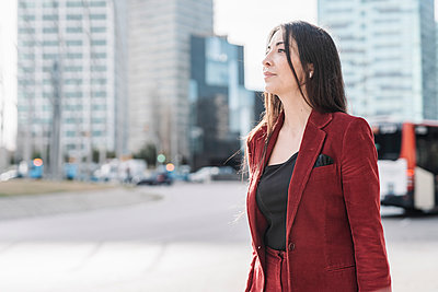 Thoughtful mature businesswoman looking away while standing in city - p300m2265922 by COROIMAGE