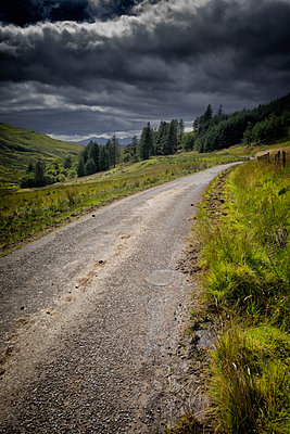 Stormy landscape cloudy dramatic hills forest road - p609m1219848 by OSKARQ