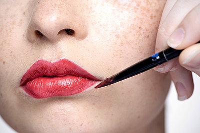 Young woman applying lipstick with lip brush, close-up - p623m923100f by Milena Boniek