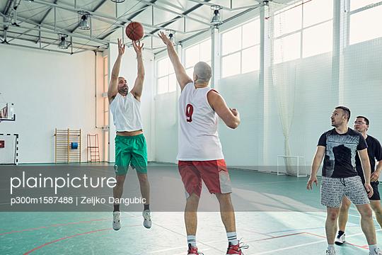 Men playing basketball, indoor - p300m1587488 von Zeljko Dangubic