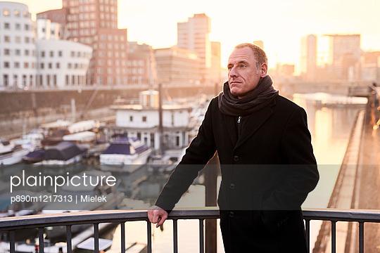 Mann auf einer Brücke im Medienhafen - p890m1217313 von Mielek