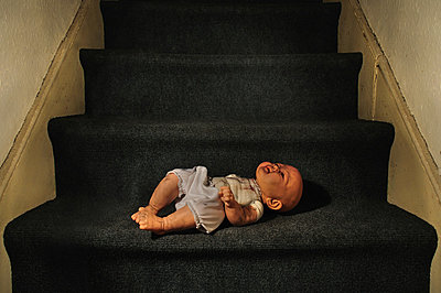 Broken doll laying on stairs  - p1072m829358 by Neville Mountford-Hoare