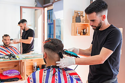 Male hairstylist cutting hair of customer with machine in salon - p300m2275543 by Julio Rodriguez