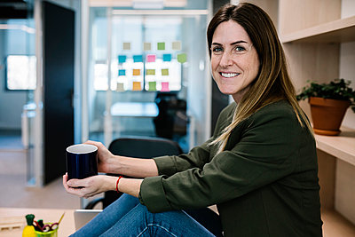 Businesswoman holding mug during coffee break while sitting at office - p300m2276736 by Xavier Lorenzo