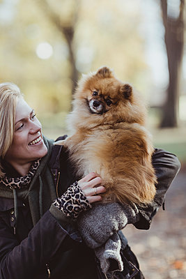 Smiling woman playing while embracing fluffy Pomeranian dog at park - p426m2194944 by Maskot
