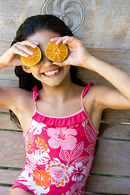 Young girl using half fruits as eyes - p42912318f by Easy Production