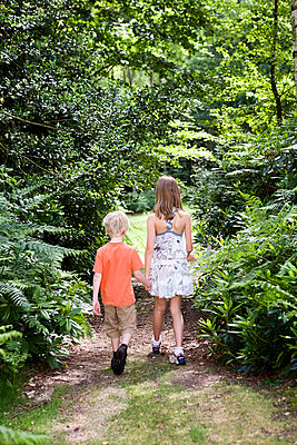 Boy and girl walking through forest - p4293241f by Karan Kapoor