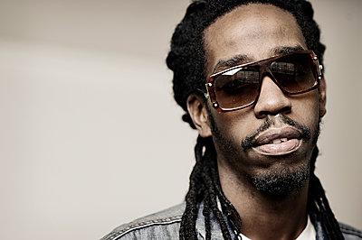 Black man wearing sunglasses - p555m1306072 by Smith Photographers