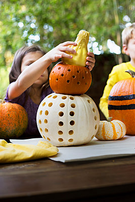 Girl and brother stacking carved pumpkins on garden table - p924m1469140 by Kinzie Riehm