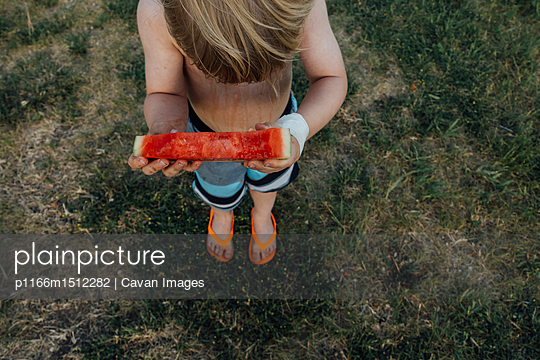 High angle view of shirtless boy eating watermelon - p1166m1512282 by Cavan Images