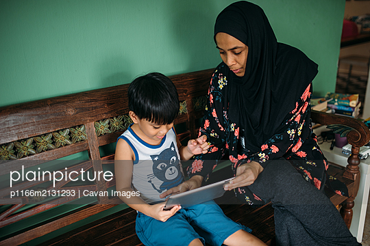 Asian mother and son playing games on smart tablet - p1166m2131293 by Cavan Images
