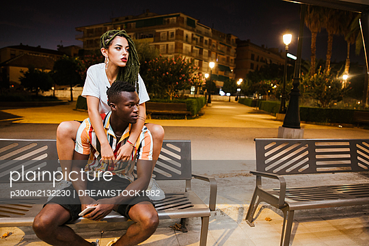 Cool young couple on a bench at night in the city - p300m2132230 von DREAMSTOCK1982