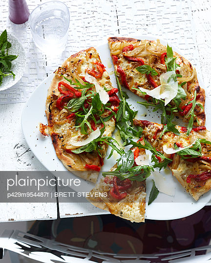 Plate of sliced wholemeal pizza with herbs, vegetable and parmesan - p429m954487f by BRETT STEVENS