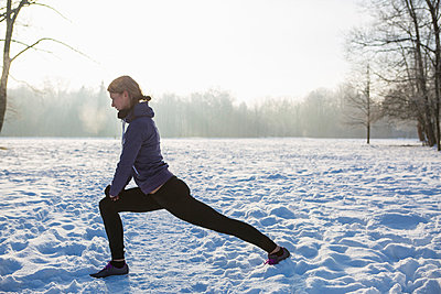 Young woman stretching in snow - p1026m1025122f by Patrick Frost
