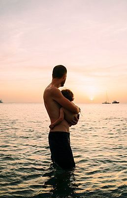 Father and little daughter watching together sunset at the sea - p300m1587881 von Gemma Ferrando