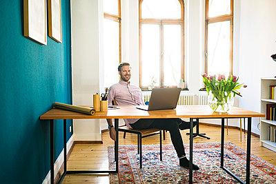 Portrait of happy relaxed casual businessman in home office - p300m2083872 by Steve Brookland
