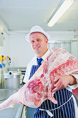 Caucasian butcher holding animal carcass in shop - p555m1410361 by Dave and Les Jacobs