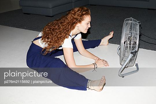 Young woman enjoys the fan - p276m2115692 by plainpicture