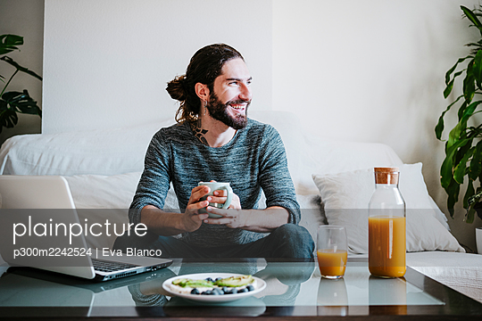 Smiling man with coffee cup looking away while having breakfast sitting on sofa at home - p300m2242524 by Eva Blanco