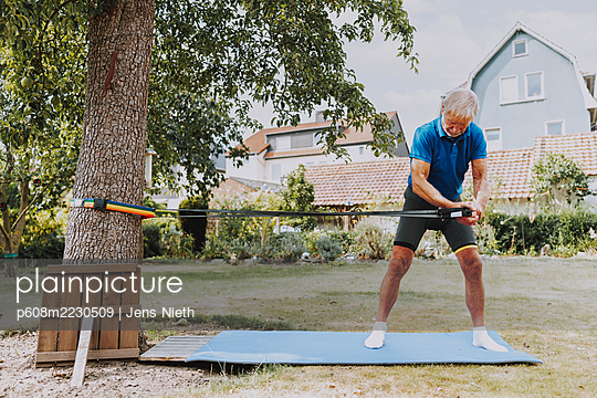 Elderly man performs sling training in the garden - p608m2230509 by Jens Nieth