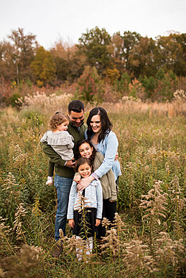 Smiling parents with daughters standing amidst plants against sky in forest - p1166m2034614 by Cavan Images
