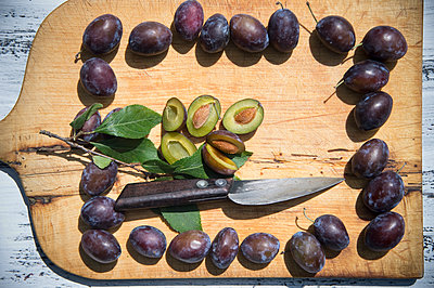 Purple plums on wooden cutting board seen from above - p300m2131734 by Achim Sass