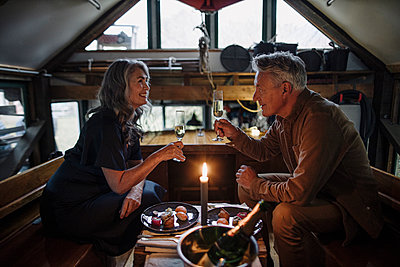Senior couple having a candlelight dinner on a boat in boathouse clinking champagne glasses - p300m2155238 von Gustafsson