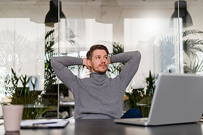 Male entrepreneur with hands behind head looking away at office - p300m2265238 by Daniel Ingold