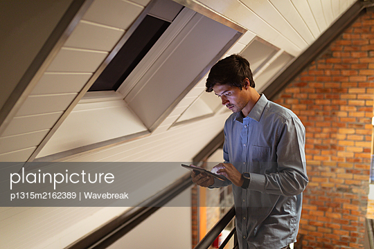 Young male business creative using tablet - p1315m2162389 by Wavebreak