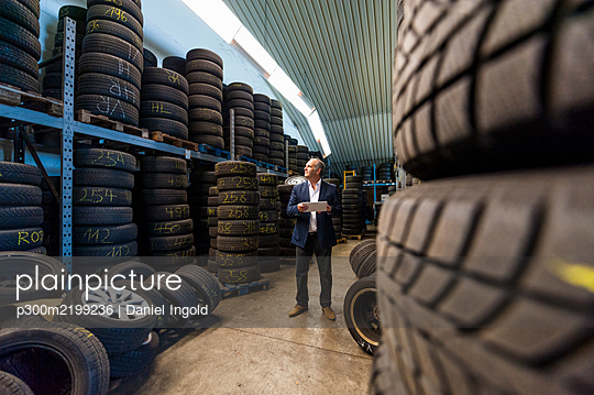 Male entrepreneur checking tire stacks at store - p300m2199236 by Daniel Ingold