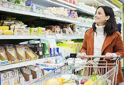 Smiling woman shopping in supermarket - p1023m2187687 by Robert Daly