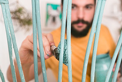 Bearded man painting wicker armchair at home - p300m1449239 by Retales Botijero