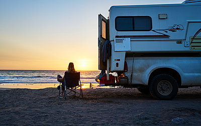 Chile, Arica, woman sitting next to camper on the beach at sunset - p300m2069127 by Stefan Schütz