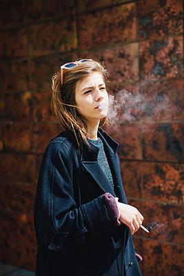 Woman smoking cigarette - p586m1044690 by Kniel Synnatzschke