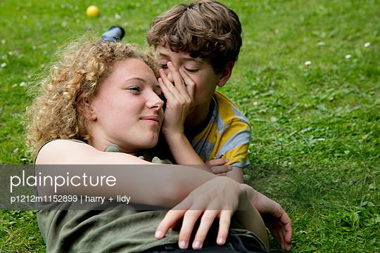 Junge flüstert Mädchen etwas im Ohr - p1212m1152899 von harry + lidy