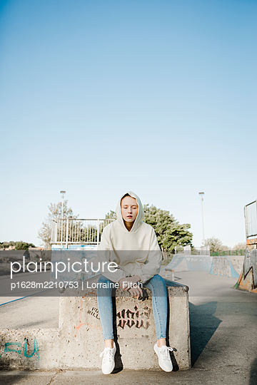 Teenage girl in hooded shirt sitting on concrete wall - p1628m2210753 by Lorraine Fitch