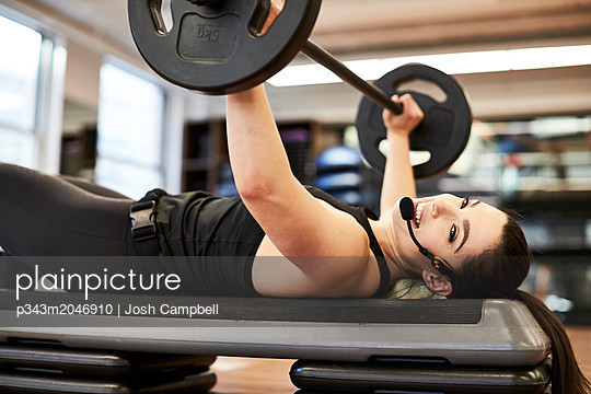 Fitness instructor doing bench press - p343m2046910 by Josh Campbell