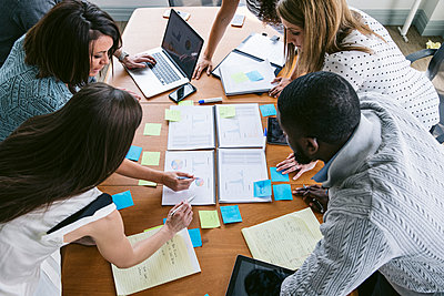 High angle view of business people brainstorming in board room - p1166m1414594 by Cavan Images