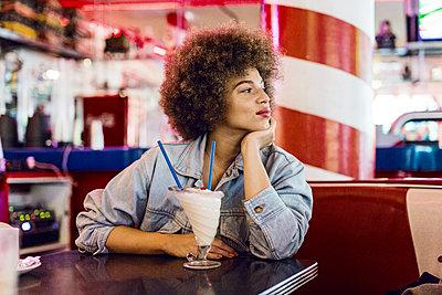 Junge Frau mit Afro in American Diner - p1301m1467397 von Delia Baum