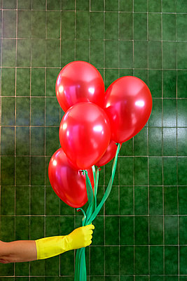 Hand in yellow plastic gloves holding red balloons - p1521m2126556 by Charlotte Zobel