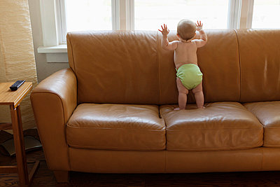 Baby boy playing on sofa - p429m817507 by Roberto Westbrook