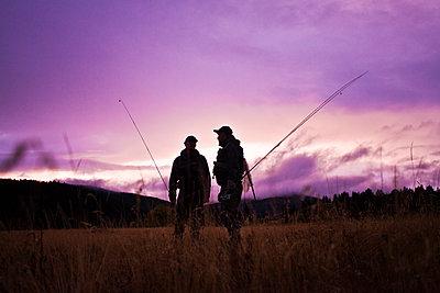 Caucasian men carrying fishing rods - p555m1301786 by Mike Kemp