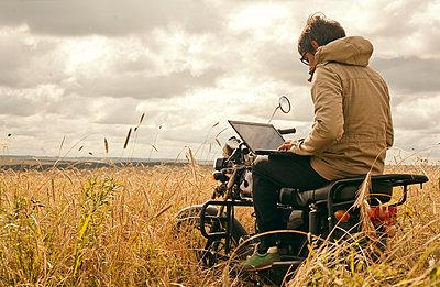 Mari man using laptop on motorcycle in rural field - p555m1420527 by Aliyev Alexei Sergeevich