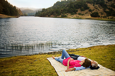 Couple laying on blanket near lake - p555m1532674 by Caterina Bernardi