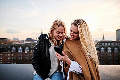 Zwei Freundinnen schauen auf ein Smartphone - p890m2231035 von Mielek